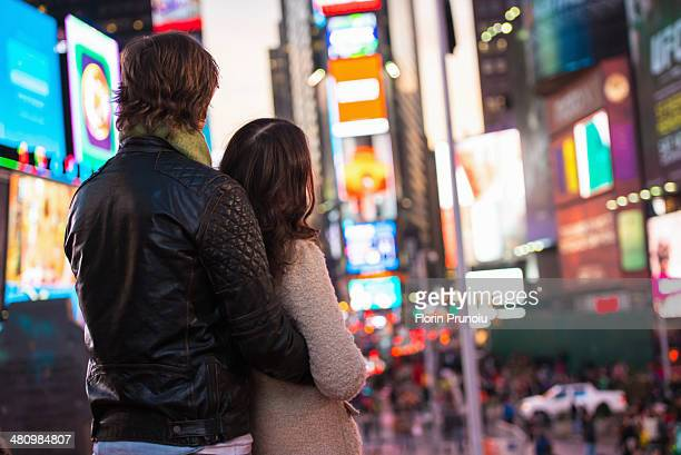 Young couple looking up at neon signs, New York City, USA