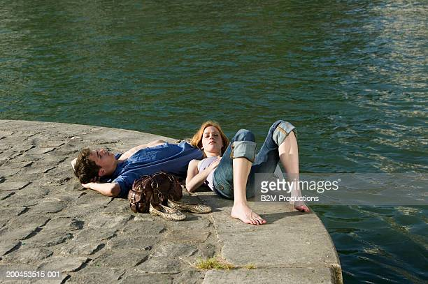 Young couple lying at edge of quay, woman resting head on man's leg