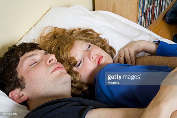 A young couple lying in bed together