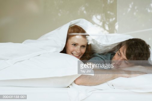 Young couple lying in bed under duvet, smiling, view through window : Foto de stock
