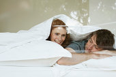 Young couple lying in bed under duvet, smiling, view through window