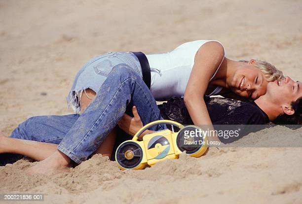 Young couple lying in embrace on sand beside radio