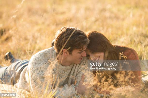 Young couple lying in field, smiling