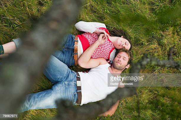 Young couple lying in meadow, eyes closed, elevated view