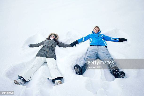 young couple lying in snow doing snow angels