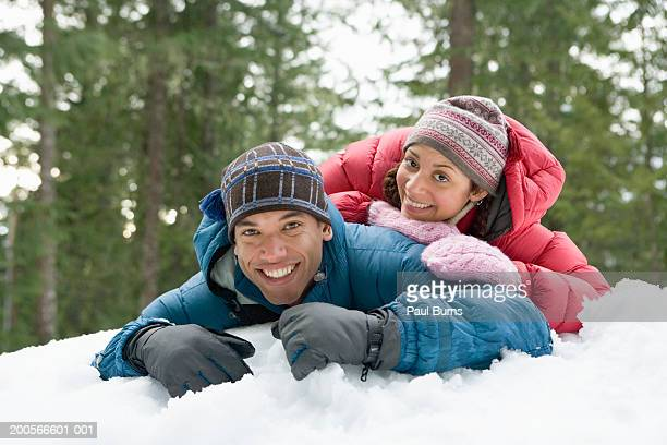 Young couple lying in snow, smiling, portrait