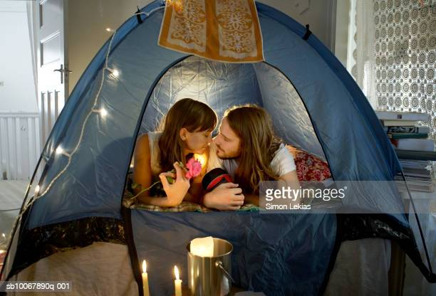 Young couple lying in tent rubbing noses, woman holding rose flower