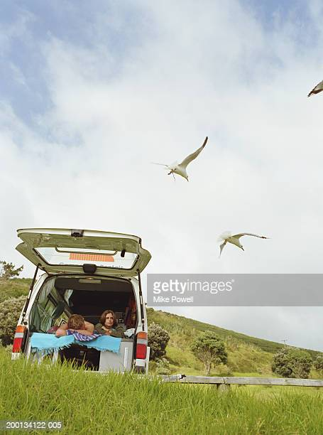 Young couple lying inside camper van