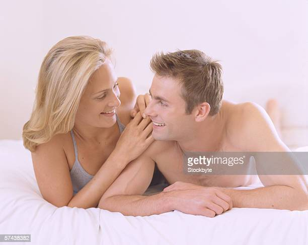 Young couple lying on a bed looking at each other smiling