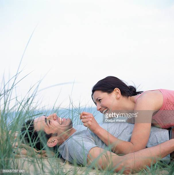 Young couple lying on beach, woman tickling man with grass, smiling