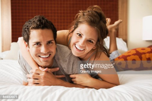 Young couple lying on bed, looking at camera. : Bildbanksbilder