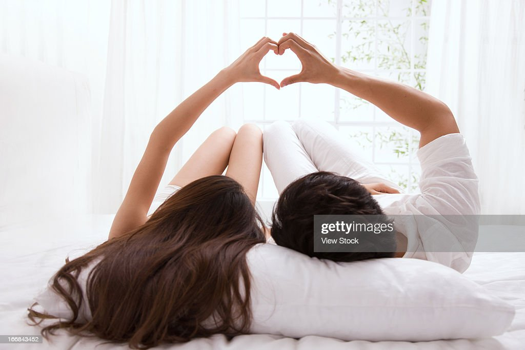 Young couple lying on bed : Stock Photo