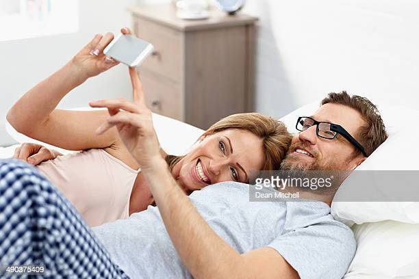 Young couple lying on bed using mobile phone