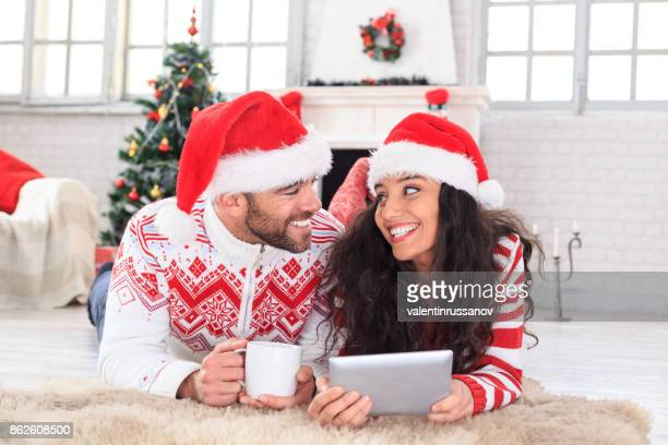 Young couple lying on front and making selfie at home