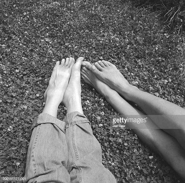Young couple lying on grass, low section (B&W)