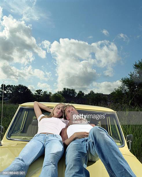 Young couple lying on hood of pick-up truck, eyes closed