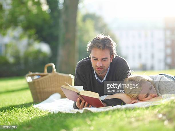 Young couple lying on lawn in park, man reading book, woman sleeping
