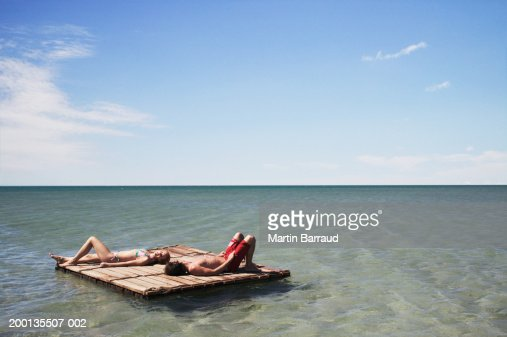 Young couple lying on raft at sea