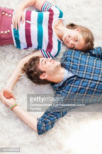 Young couple lying on rug holding hands : Stock Photo