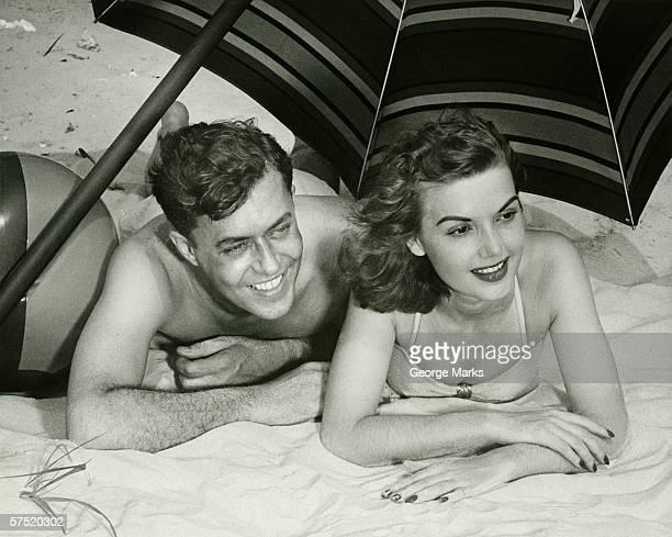 Jeune couple Allongé sur le sable, sous un parasol, souriant, (B & W