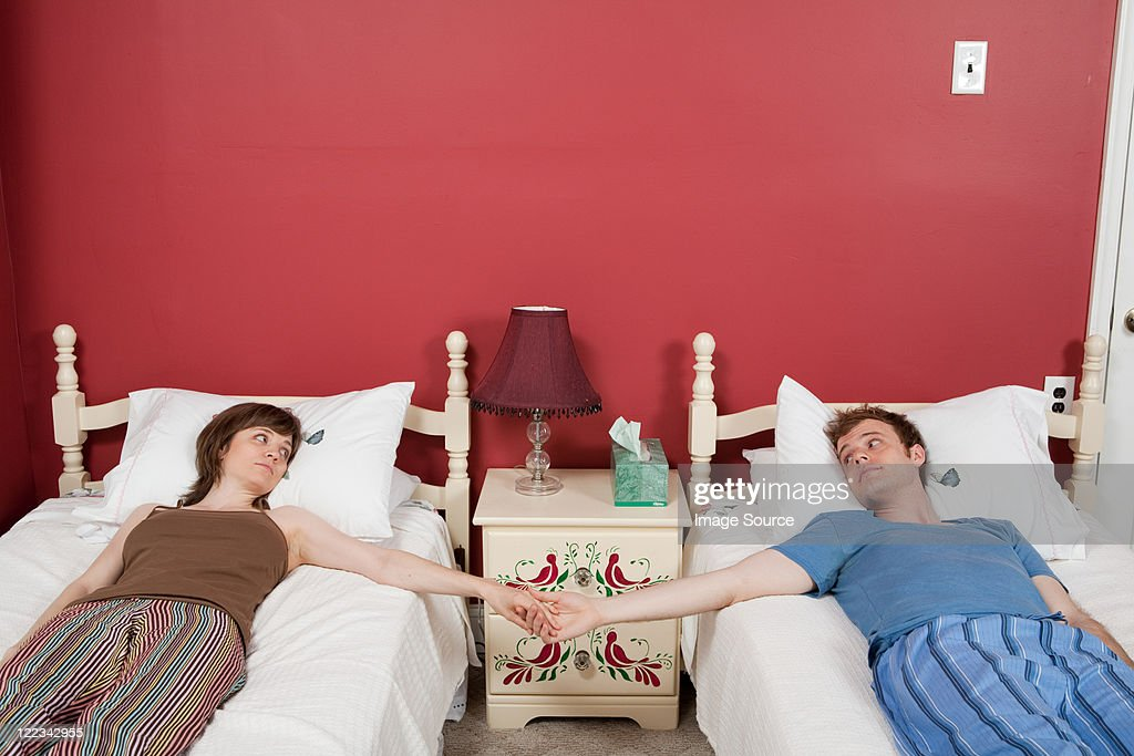 Young couple lying on single beds, holding hands