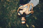 Young couple lying on the grass with sunglasses on sunny day