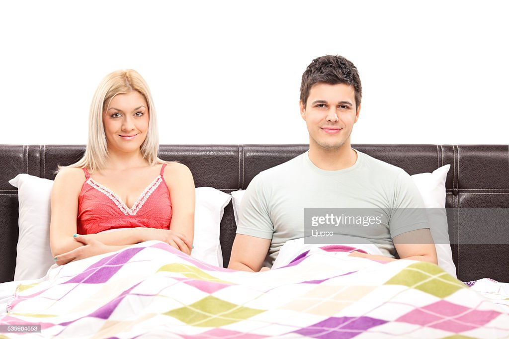 Young couple lying together in bed : Stock Photo