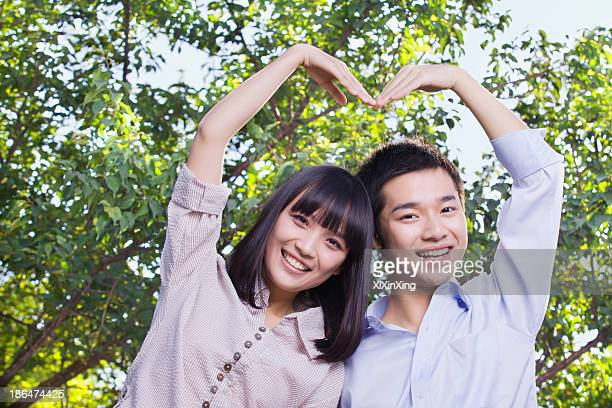 Young Couple Making a Heart Shape with Their Arms