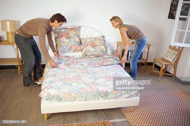 Young couple making bed, smiling