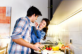 Young couple making breakfast early in the morning in the kitchen and having a good time.