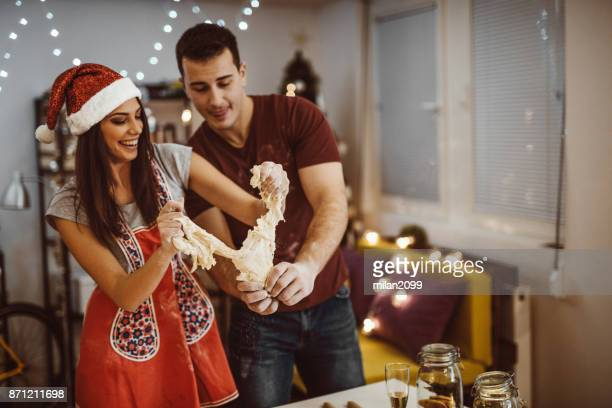 Young couple making christmas cookie from dough in the kitchen