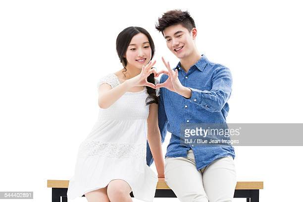 Young couple making heart shape with their hands
