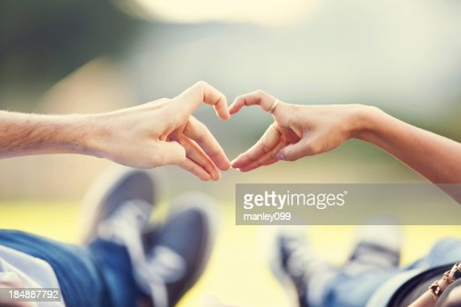 young couple making heart sign