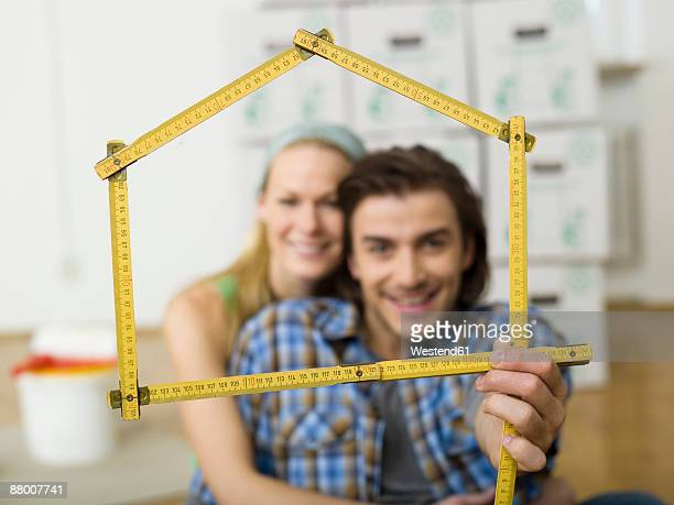 Young couple making house shape with folding ruler, smiling, portrait