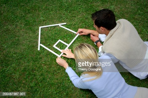 Young couple making house shape with rulers on grass : Stock Photo