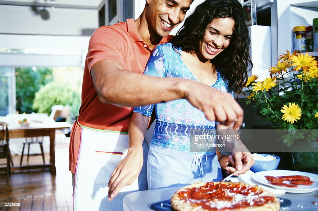 Young couple making pizza in kitchen : Stock Photo