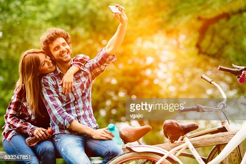 Young couple making selfie after riding bicycle outdoors.