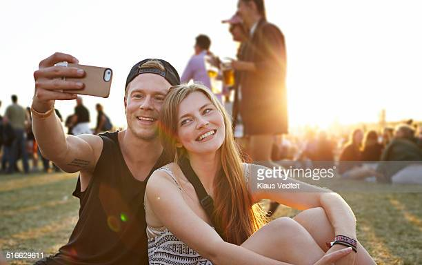 Young couple making selfie at big festival