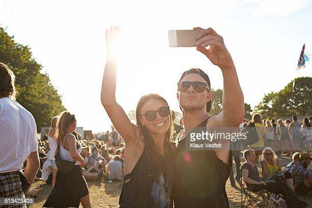Young couple making selfie at festival