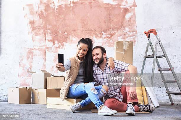 Young couple making selfie at new home