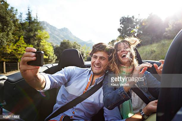 Young couple making selfie on the backseat of car