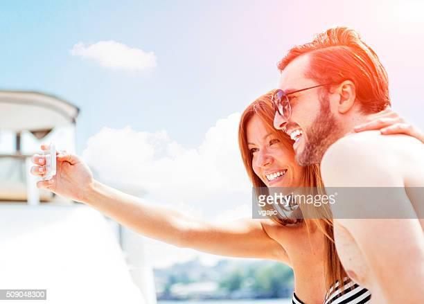 Junge Paare, die Selfie auf der Jacht und Spaß haben