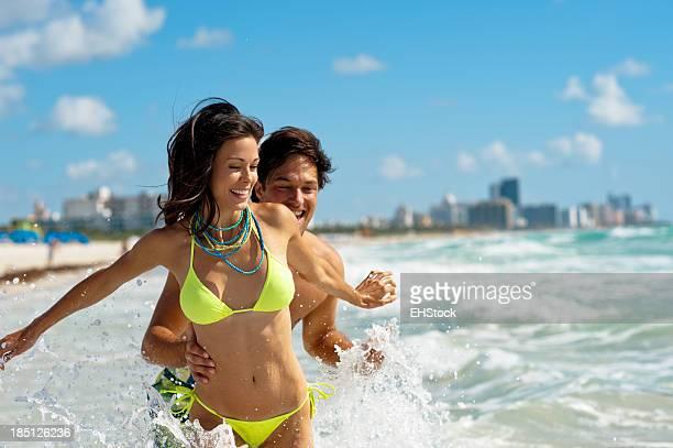 Pareja joven hombre y mujer jugando en el Surf en la playa
