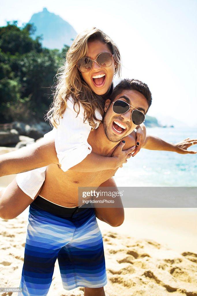 Young couple, man piggyback a beautiful woman on the beach. : Stock Photo