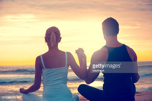 Young couple meditating on the beach.