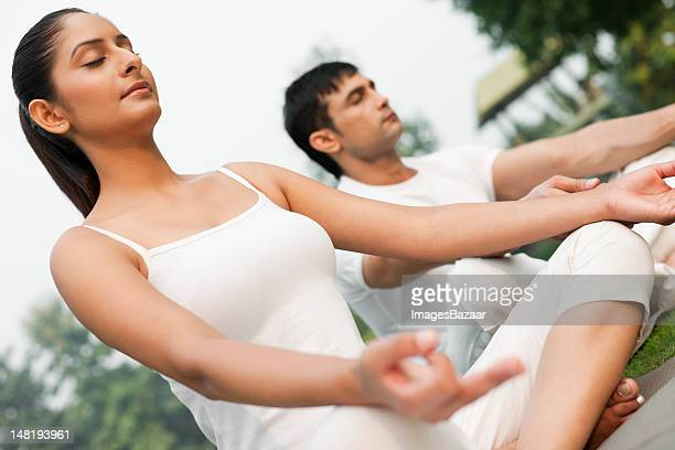Young couple meditating outdoors