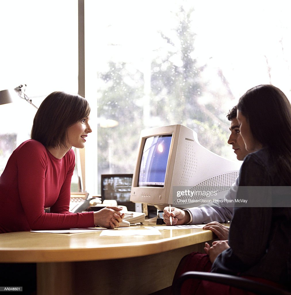 Young couple meeting with woman at desk, side view : Stock Photo