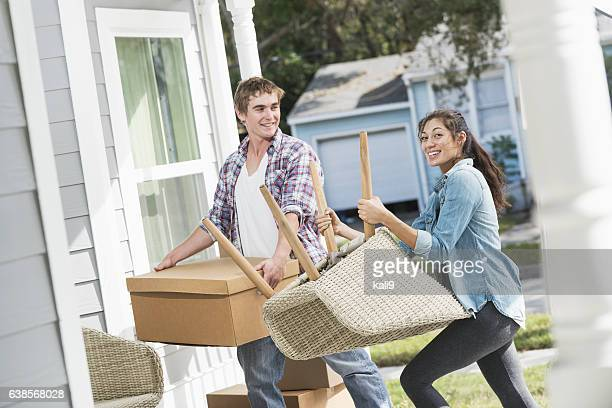Young couple moving boxes and furniture into new home
