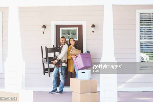 Young couple moving, carrying belongings thru front door
