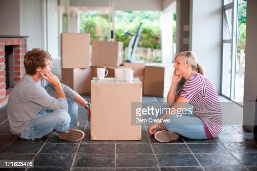 Young couple moving house sitting on floor with box